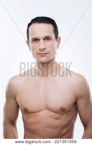 Keeping fit. Handsome nice well built man smiling and looking at you while keeping fit