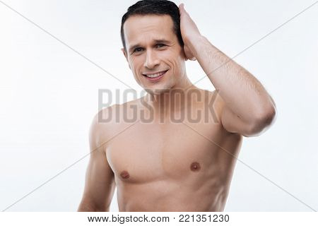 I am handsome. Joyful nice handsome man touching his hair and smiling while being confident in himself