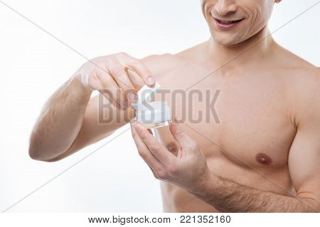 Perfect skin moisturizer. Close up of a moisturizing cream bottle being opened by a happy delighted nice man