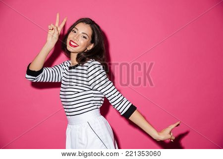 Portrait of a smiling woman showing peace gesture with two hands isolated over pink background