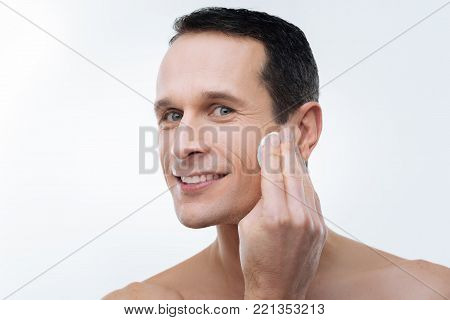 Looking good. Portrait of a handsome delighted man using a cotton pad while cleaning his skin