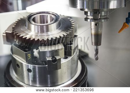 The CNC milling machine cutting the sample  gear part.The mechanical part manufacturing process by CNC milling   machine.Modern manufacturing process.