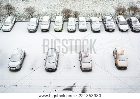 Ground parking cars after snowfall, view from above. Automobiles covered with snow, the traces of wheels.