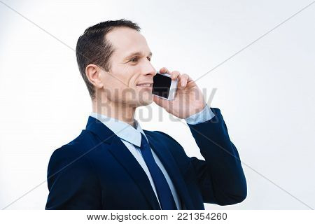 Business issues. Joyful nice professional businessman smiling and talking on the phone while discussing business issues