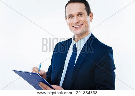 Favourite occupation. Cheerful nice positive businessman looking at you and writing notes while being happy about his job