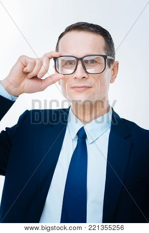 My success. Serious ambitious smart businessman touching his glasses and looking at you while thinking about his professional success