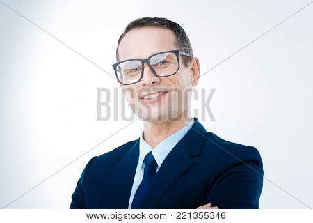 I am the boss. Cheerful nice delighted man smiling and looking at you while being the boss