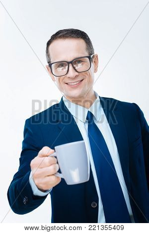 Try it. Joyful intelligent positive businessman smiling and looking at you while offering a cup of coffee