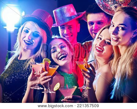 Woman disco night club. Dance party with group people dancing. Female and men have fun. Rest after hard day at work. Drinking fruit alcohol at private party.