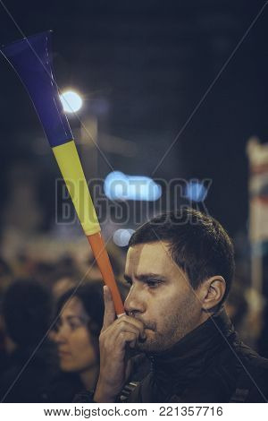 Bucharest, Romania - October 6, 2013: Young man blows a vuvuzela during the population uprising against the cyanide gold extraction in the Europe's largest open-pit gold mine planned to be opened in Rosia Montana heritage site, Alba County, Romania.