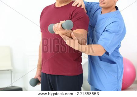 Senior man doing exercise under supervision of physiotherapist, closeup