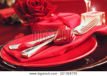 St. Valentines day dinner. Valentines day table setting in rustic elegant style with cutlery. Romantic dinner