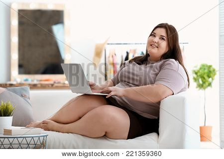 Beautiful overweight woman with laptop indoors