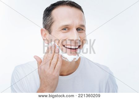 Ready for shaving. Delighted happy handsome man applying shaving foam and smiling while being ready for shaving