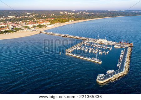 Sopot resort in Poland. Wooden pier (molo) with marina, yachts, beach, pirate tourist ship, vacation infrastructure, hotels, parks and promenades. Aerial view at sunrise.