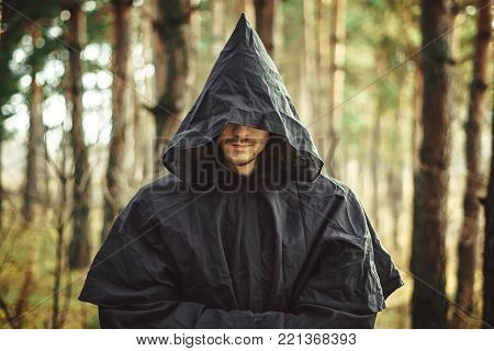 A creepy man in a black hood in the forest