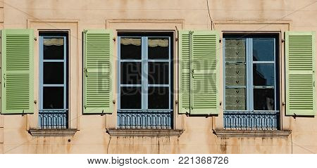Open and shut old style windows with colorful wooden shitters and french-style balconies