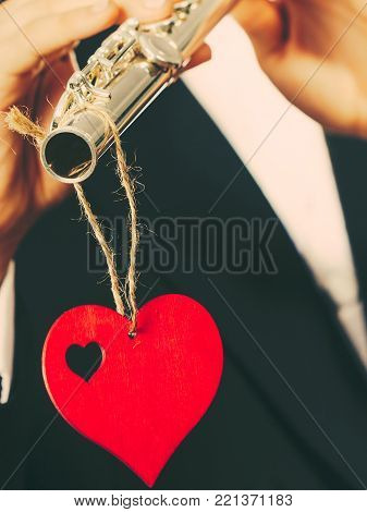 Valentines day love melody concept. Flute music playing man flutist musician performer. Male hands with instrument and red heart, close up