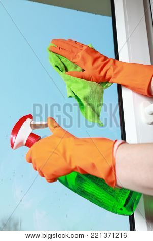 hand in orange glove cleaning window with green rag and spray detergent. Spring cleaning concept