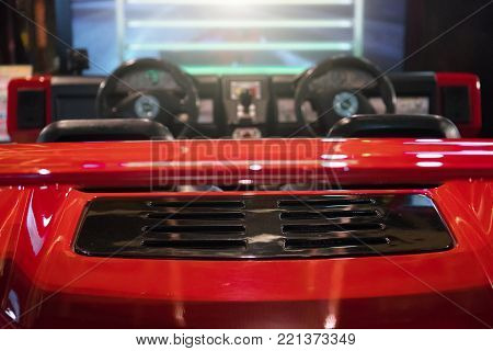 Red racing simulator game in theme park.