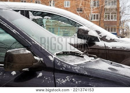 Parked cars covered with snow. Car under the snow. Selective focus
