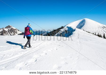 Sporting woman in mountains, Background hiker in mountains, Snowy mountains with tourist, Woman on mountain top, Concept ascent to top of mountain, Walking in mountains