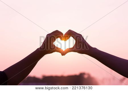 Heart symbol silhouette by woman and man hands together direct to morning pink love sun light with empty copy space over sky for text, wordings, logo insertion or decoration, Valentine's day holiday