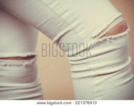 Tight white trousers pants jeans with holes on knees, female fashion concept.