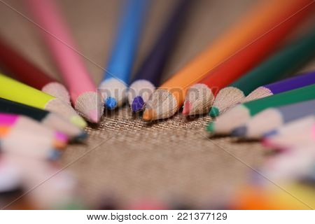 Multicolored pencils on the table. A stack of colored pencils tied together. A scattering of writing supplies and stationery.