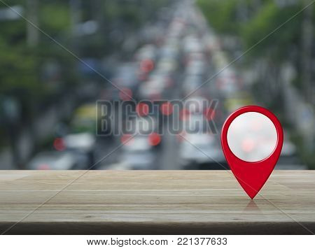 Map pin location button on wooden table over blur of rush hour with cars and road, Map pointer navigation concept