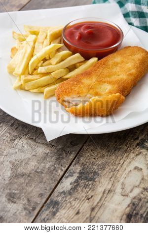 Traditional British fish and chips on wooden table.