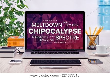 Chipocalypse concept with meltdown and spectre threat. Chipocalypse vulnerability concept with meltdown and spectre threat on laptop screen in office workspace with different gadgets on the desk.