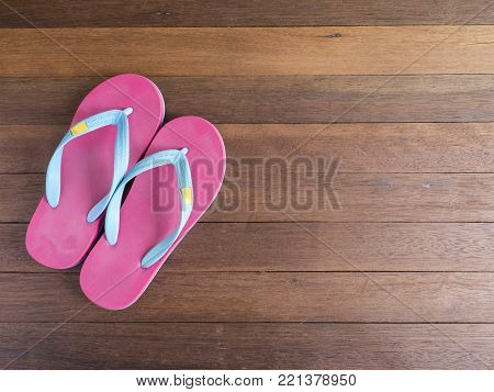 Pink flip flop / pink slipper on wooden floor on top view