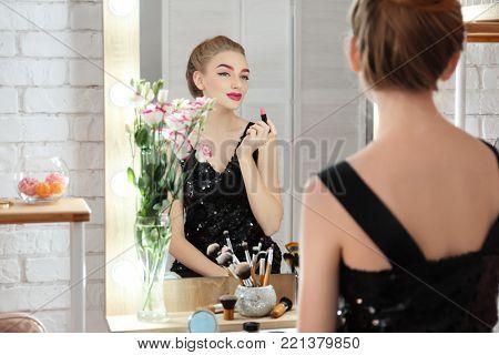 Young beautiful woman applying makeup near mirror in room
