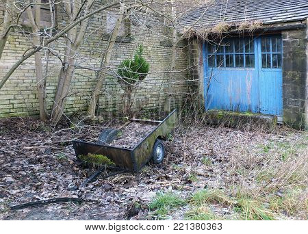 Abandoned Derelict Farming Trailer Covered In Moss And Dead Leaves Outside A Derelict Farm Building