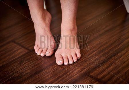 Close up beutiful bare feet on dark wooden floor