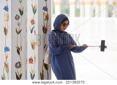 ABU DHABI, UNITED ARAB EMIRATES - DEC 28, 2017: A muslima is making a selfie with her smartphone in the Sheikh Zayed Mosque in Abu Dhabi. It is the largest mosque in the country.