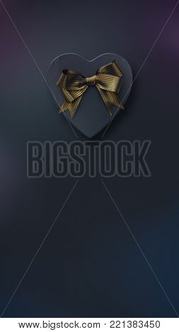 Vertical banner with black heart shaped gift box with golden bow on black. Top view. 3D render