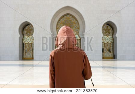 ABU DHABI, UNITED ARAB EMIRATES - DEC 28, 2017: A veiled muslima woman in the Sheikh Zayed Mosque in Abu Dhabi. It is the largest mosque in the country.