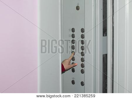 Female hand presses the seventh floor button on the panel of the Elevator when the doors are open