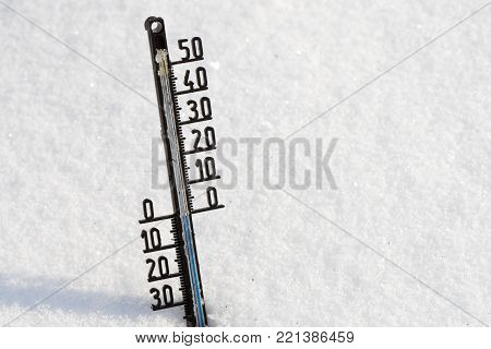 Thermometer on snow shows low temperatures under zero in degrees Celsius