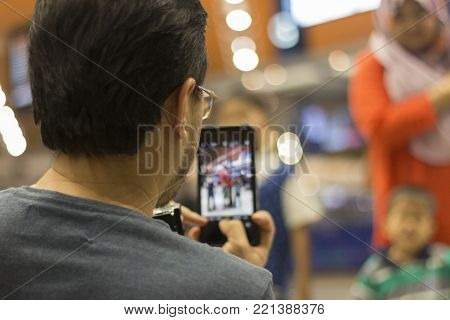 Man Capturing Photo Of His Family Using Iphone.