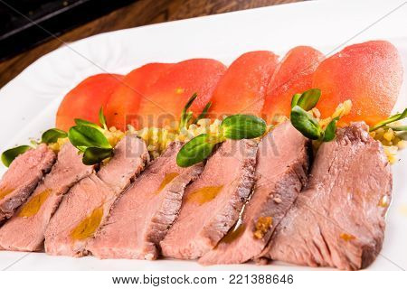 Roast beef with tomatoes and bulgur on white plate