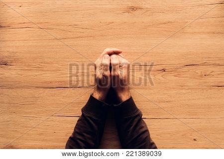 Man praying, overhead view of male hands on wooden church prayer kneeler