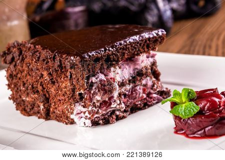 Chocolate piece of cake with cherry on white plate