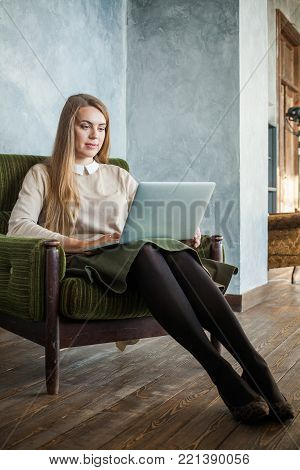 Cheerful Girl Using Laptop, Internet Shopping or Social Media Concept. Young Smiling Woman Surfing the Web
