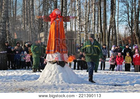 TULA, RUSSIA - MARCH 3, 2016: Traditional burning of Maslenitsa Scarecrow on seeing Russian winter on last day of Shrovetide. Worker of fire safety begins ignition of stuffed