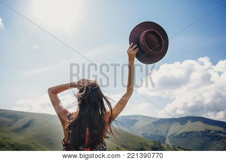 stylish traveler woman looking at mountains. hipster girl on top of mountain, raising hands and holding hat in sky. space for text. atmospheric epic moment. wanderlust and travel concept poster