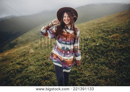 happy traveler girl in hat with backpack standing in mountains. hipster woman smiling on top of windy mountain. space for text. wanderlust and travel concept. atmospheric epic moment