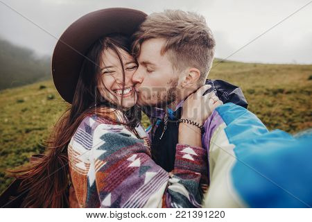stylish traveler couple taking selfie photo in mountains. hipster man and woman with windy hair in hat smiling and kissing. space for text. wanderlust and travel concept. atmospheric moment poster